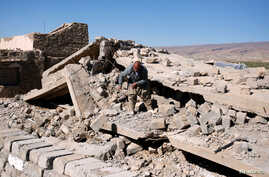 FILE - A Yazidi man walks on the ruins of his house, destroyed by Islamic State militants near Sinjar, Iraq, Feb. 5, 2019.