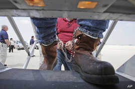 FILE - Shackled Mexican nationals are boarded onto a U.S. Immigration and Customs Enforcement jet for deportation, at O'Hare International Airport in Chicago, Illinois, May 25, 2010.