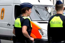 FILE - Police officers stand near a bomb squad van in central Antwerp, Belgium, June 18, 2016. Belgian police raided 15 homes in the cities of Antwerp, Ghent and Deinze, taking 15 people in for questioning.