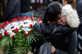 Mourners hug each other during a state funeral for some of the victims of last Wednesday's earthquake, in Amatrice, central Italy,  Aug. 30, 2016.