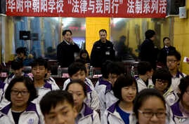 """Government workers stand under a banner that reads """"Tsinghua affiliated Chaoyang School, The Law and me together, legal series of talks"""" as they observe a student meeting on legal matters on China's first Constitution Day in Beijing, Dec. 4, 2014."""