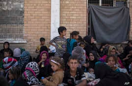FILE - Women and children from Hawija sit outside a Kurdish screening center to determine if they were associated with the Islamic State group, in Dibis, Iraq, Oct. 3, 2017.