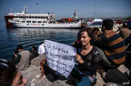 A woman activist holds a placard as a small Turkish ferry carrying migrants who are deported to Turkey arrives on April 4, 2016 at the port of Dikili district in Izmir.
