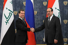 Russian Prime Minister Dmitry Medvedev shake hands with Iraq's Prime Minister Nouri Al-Maliki, right, prior to their meeting in the Gorki residence outside Moscow, October 9, 2012.