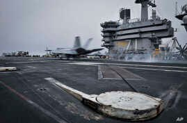 In this Wednesday, April 15, 2015 image released by U.S. Navy Media Content Services, an F/A-18E Super Hornet, assigned to the Knighthawks of Strike Fighter Attack Squadron 136, lands on the flight deck aboard Nimitz-class aircraft carrier USS Theodo