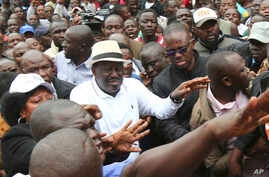 Kenya's opposition leader, Raila Odinga, centre, joins his supporters in the Mathare area where four people were killed overnight, in Nairobi, Nov. 19, 2017.