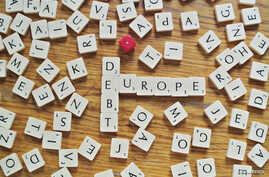 The words debt and Europe, made from letters of a scrabble game, are seen in this illustration.