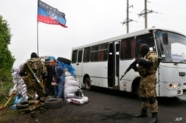 """Pro-Russia masked armed militants check luggage from a passenger bus at a checkpoint near Slovyansk, eastern Ukraine, April 30, 2014. The flag reads """"Donetsk Republic,"""" which some separatists already see as independent from Ukraine."""