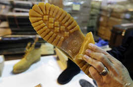 FILE - U.S. Customs and Border Protection Deputy Chief Officer Stephen Long shows how a Timberland brand on a counterfeit boot is hidden at a warehouse in Kearney, N.J., Oct. 28, 2015.