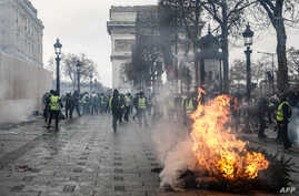 Protesters wearing yellow vests stand next to a burning tree as they demonstrate against the rising costs of living that they blame on high taxes near the Arc de Triomphe on the Champs-Elysees avenue in Paris, Dec. 8, 2018.