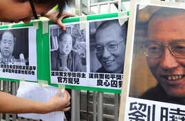 A protester affixes pictures of Chinese writer Mo Yan (L) and Chinese dissident Liu Xiaobo (R) to a gate during a demonstration in front of the Chinese liaison offices demanding the release of Chinese Liu in Hong Kong on October 13, 2012.  China's No