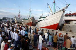 Muslims attend an Eid al-Fitr mass prayer to mark the end of the holy fasting month of Ramadan at Sunda Kelapa port in Jakarta, Indonesia, June 25, 2017.