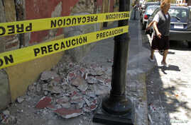 FILE - A resident evades rubble after an earthquake, in Oaxaca, March 20, 2012.