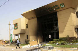 A man passes a bank building burnt during protests over cooking oil and fuel subsidy cuts in Khartoum September 26, 2013.