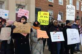 Protesters gather outside Jefferson Middle School in Washington, Feb. 10, 2017, where Education Secretary Betsy DeVos paid her first visit as education secretary in a bid to mend fences with educators after a bruising confirmation battle.