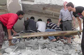 This citizen journalism image shows Syrian citizens searching under rubble to rescue people from a building that was destroyed from a Syrian forces airstrike, at Kfar Nebel town, in Idlib province, northern Syria, October 17, 2012.