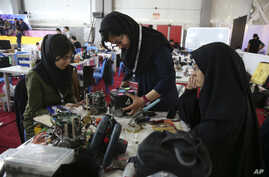 FILE - In this April 6, 2016, file photo, Iranian students prepare their robots during the international robotics competition, RoboCup Iran Open 2016, in Tehran, Iran. Universities in the U.S. say President Donald Trump's revised travel ban would blo