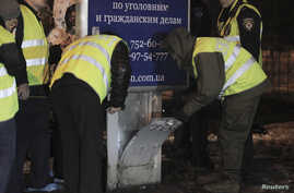 Investigators work at a blast site near a court house in Kharkiv January 19, 2015. Six people were treated in hospital for injuries on Tuesday after what police said was a grenade attack on a group of Ukrainian nationalists in the eastern city of Kha