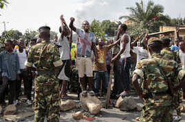 FILE - Oposition demonstrators confront army soldiers in the Mutarakura district, as security forces try to prevent people from moving out of their neighborhoods, in the capital Bujumbura, Burundi.