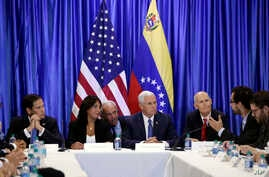 Vice President Mike Pence, second from right, listens with Sen. Marco Rubio, R-Florida., left, Venezuelan exile Maria Eugenia Tovar, and Florida Gov. Rick Scott, right, as a former political prisoner from Venezuela speaks at Our Lady of Guadalupe Cat
