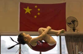 A young gymnast trains near the Chinese national flag at the Xuhui Sports School in Shanghai, China, June 16, 2016.