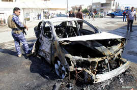 Iraqi security forces inspect the site of a bomb attack, after a parked motorcycle blew up, in Kirkuk, Oct. 13, 2014.
