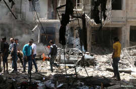 People inspect the damage at a site hit by airstrikes, in the rebel-held area of Aleppo's Bustan al-Qasr, Syria, April 28, 2016.