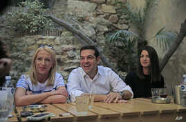 Syriza left-wing party leader and former Prime Minister Alexis Tsipras, centre, laughs as he meets with young people at a coffee shop, in central Athens, Sept. 19, 2015, ahead of Sunday, Sept. 20, 2015 elections.