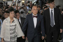 Donald Tsang, center, former leader of Hong Kong and his wife Selina arrive at a magistrates' court in Hong Kong Monday, Oct. 5, 2015.