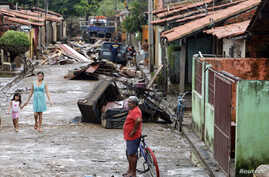FILE - Residents walk on a street which was flooded by the Poti river in Teresina in the northeastern Brazilian state of Piaui, May 8, 2009.
