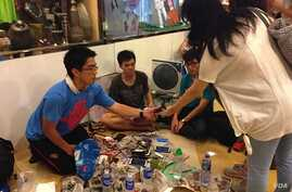 "Student volunteers offer a free phone charging service at ""Charging Corner"" inside Hong Kong's occupied central business district. The students have adapted a multi-USB powerboard, and can charge up to 80 telephones from one electric socket, Oct. 8,"