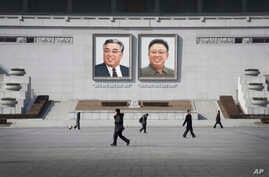 FILE - People walk past portraits of the late North Korean leaders Kim Il Sung and Kim Jong Il at Kim Il Sung Square in Pyongyang, North Korea.