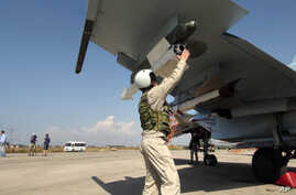 In this photo taken on Oct. 5, 2015, a Russian pilot fixes an air-to-air missile at his Su-30 jet fighter before a take off at Hmeimim airbase in Syria.