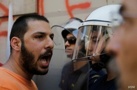 """A member of the Communist-affiliated PAME labor union shouts slogans at the police during an anti-austerity protest calling to """"Vote NO"""" outside of the in central Athens, on July 3, 2015."""