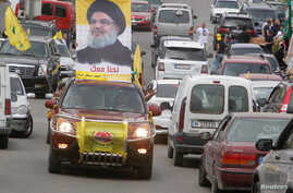 A man gestures as he drives a car with the picture of Hezbollah leader Sayyed Hassan Nasrallah on it, during the parliamentary election day, in Bint Jbeil, southern Lebanon, May 6, 2018.