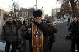 Priest is overcome with emotion as he holds memorial service for protesters killed during clashes with police, near Independence Square, Kiev, Feb. 21, 2014.