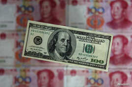 FILE - A photo illustration shows a $100 banknote placed above Chinese 100 yuan banknotes in Beijing.