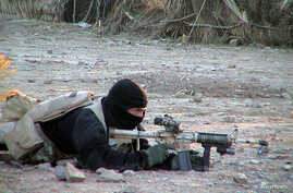 A U.S. Navy SEAL member provides cover for his teammates advancing on asuspected location of al-Qaeda and Taliban forces, January 26, 2002.Navy special operations forces are conducting missions in Afghanistanin support of Operation Enduring Freedom.