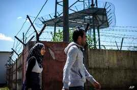 Illegal migrants walk toward the city center next to the fence around the refugee camp in Debrecen, 221 kms  from Budapest, July 1, 2015.