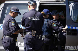 Police talk outside a house that was involved in pre-dawn raids in the western Sydney suburb of Guilford, September 18, 2014.
