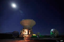 FILE - Moon shines over Chilean radio antennas that link as a single giant telescope, much like components of planned project in Mauana Kea, on Hawaii's Big Island.