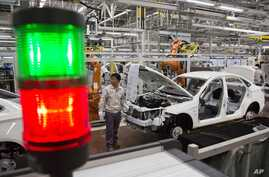 FILE - A worker assembles a car at a factory for Chinese automaker BAIC Motor in Beijing.