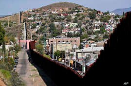 FILE - The United States-Mexico international border cuts through Nogales, Ariz., with Nogales, Ariz., left, and Nogales, Sonora, Mexico. The U.S. military put six rows on concertina wire on top of the two-story wall. The city council of Nogales, Ari