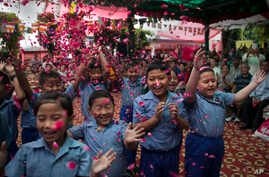 Exiled Tibetan school children throw flowers in the air as they sing a birthday song to celebrate their spiritual leader, the Dalai Lama's' 80th birthday in New Delhi, India, July 6, 2015.