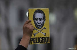 A protester holds a sign with an image of former president Alberto Fujimori with the word 'Danger' during a march against a possible pardon for Fujimori, who has been serving a 25-year sentence for human rights violations, in Lima, Peru, July 7, 2017