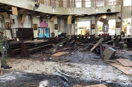 A soldier views the inside of the Roman Catholic cathedral in Jolo, the capital of Sulu province in the southern Philippines, after two bombs exploded, Jan. 27, 2019, in this photo provided by WESMINCOM Armed Forces of the Philippines.