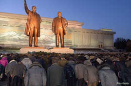 North Koreans bow to bronze statues of North Korea's late founder Kim Il Sung (L) and late leader Kim Jong Il at Mansudae in Pyongyang in this picture provided by Kyodo, December 16, 2014.