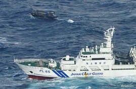 FILE - A Japan Coast Guard vessel sails near a drifting wooden boat carrying men identified as North Koreans off Matsumae town, on Japanese northern island of Hokkaido, in this photo taken by Kyodo, Nov. 29, 2017.
