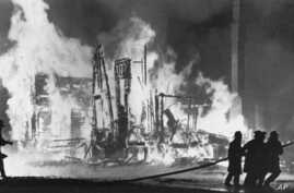 FILE - Firefighters try to control blazing buildings after riots in Detroit, July 25, 1967. Hundreds of fires were reported in the city.