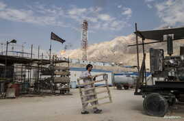 FILE - An Iranian labourer works at a unit of South Pars Gas field in Asalouyeh Seaport, north of Persian Gulf, Iran, Nov. 19, 2015.